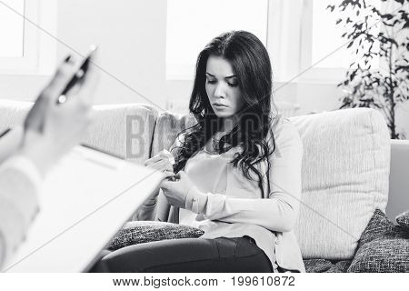 Oppressed young woman on reception at the psychologist