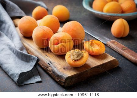 Delicious ripe apricots on a wooden stand on a dark background. Selective focus. Top view. Cope space.