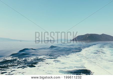 Sea View Of Skiathos Island. Waves On The Sea Left By The Ship. Vibrant Blue Sea And Sky.
