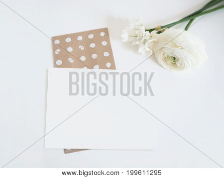 Styled stock photo. Feminine digital product mockup with buttercup and daffodil flowers, and blank list of paper . White background. Flat lay, top view. Picture for blog or social media.