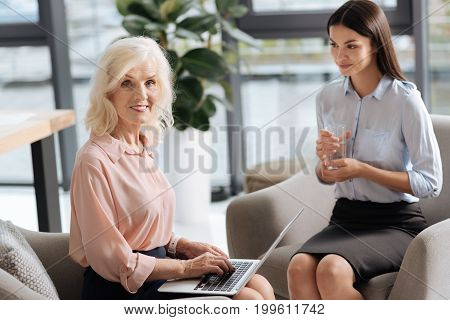 At work. Cheerful positive successful businesswoman looking at you and working on the laptop while sitting next to her personal assistant in the office