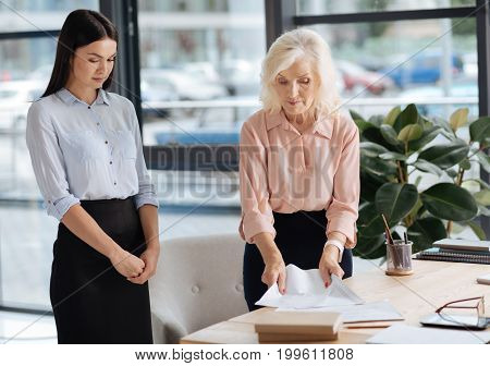 Giving instructions. Serious smart professional businesswoman standing near the table and collecting documents while giving instructions to her office manager