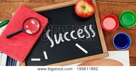 Success text against white background against overhead view of chalkboard with watercolor paints