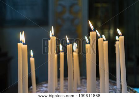 Selective focus on group of burning glowing candles light in the church.