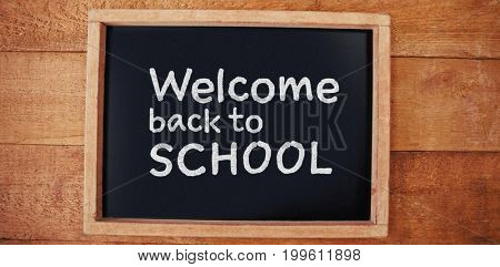 Welcome back to school text against white background against high angle view of chalkboard