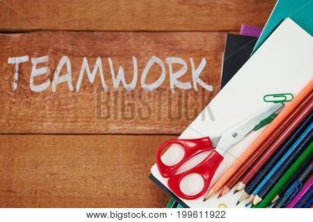 Teamwork text on white background against colorful pencils on book