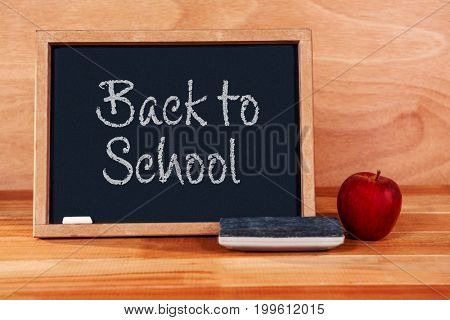 Back to school text on white background against blackboard with duster and apple