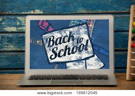 Back to school text on paper with pen against laptop on table