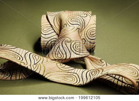 Cream Brown Necktie On Green Fabric Background, Fashion Accessory Close Up
