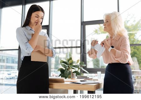 You did it wrong. Unhappy dissatisfied aged business woman shouting at her employee and tearing up the document while feeling angry about her