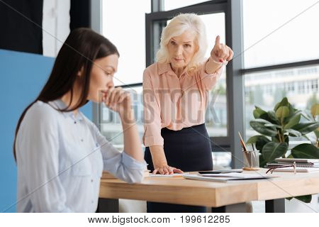 You are fired. Strict successful experienced businesswoman leaning on the table and pointing at the door while firing her employee