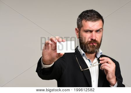 Businessman with thinking face and glasses on grey background. Guy with blank business card copy space. Success and business introduction concept. Man with beard holds white card selective focus