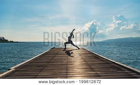 Woman silhouette practicing yoga Warrior pose on sea bridge at sunset near beach.
