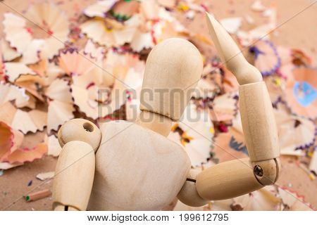 Man figurine standing amid colorful pencil shavings