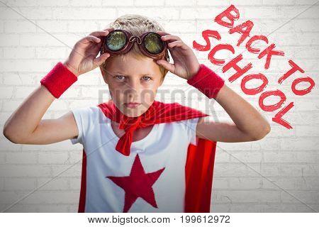 Little boy pretending to be superhero against white wall