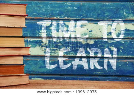 Time to learn text against white background against books on wooden table