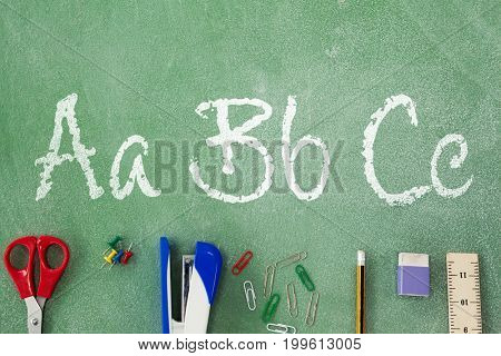 Letters on white background against overhead view of stapler with pencil on table