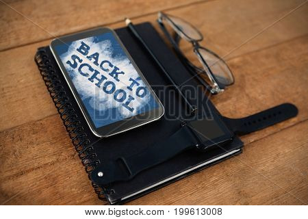 Back to school text on green and blue splash against high angle view of personal accessories