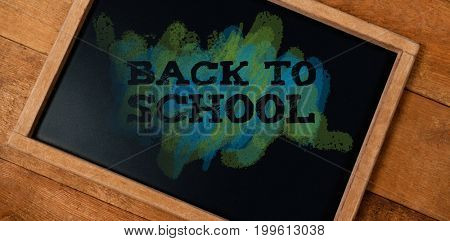 Back to school text on green and blue splash against tilt chalkboard on wooden table
