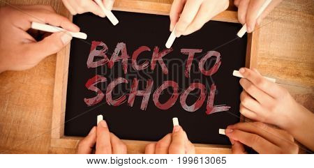 Graphic image of red back to school text against hands writing on chalkboard
