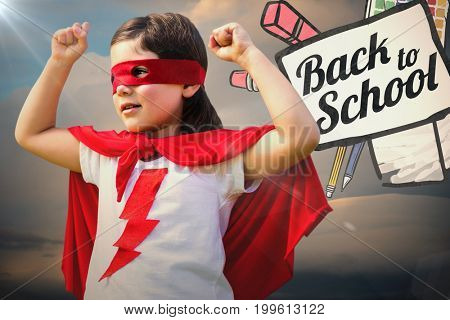 Cute girl in red eye mask and cape against cloudy sky during sunset