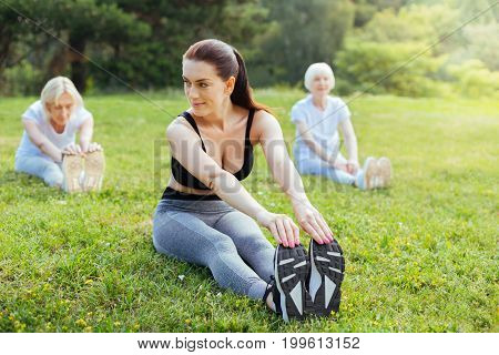 Work together. Positive instructor sitting on the grass and touching sneakers while stretching back