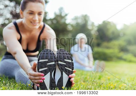 Love my sneakers. Positive delighted woman stretching her body while sitting on the grass and demonstrating it to her visitor