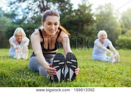 Always be in good form. Silhouettes of two elderly women sitting on the background and stretching backs while following their tutor