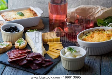 Board with basturma, salami, camembert, cheese, other delicacies and pink wine. poster