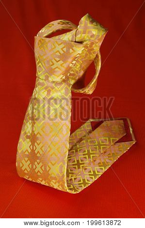 Pink And Yellow Necktie On Red Fabric Background, Fashion Accessory Close Up