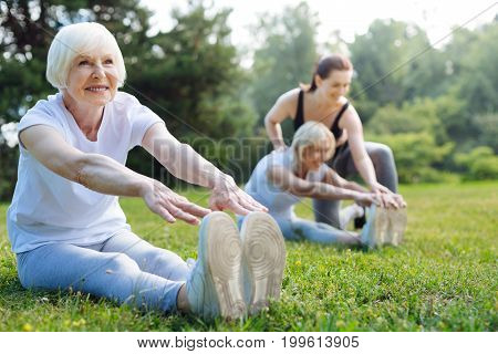 Smile on face. Happy woman sitting on the foreground and stretching her back while showing emotions