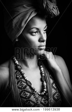 African black young woman beauty portrait with turban headscarf and traditional  clothes studio shot black and white