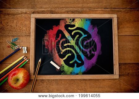Graphic image of brain on colorful splash against overhead view of blackboard with apple and pencils