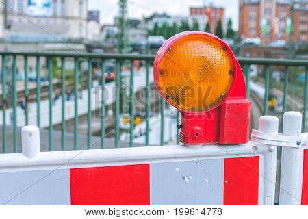 Orange construction warning street barrier light on barricade. Road construction on the streets of European cities. Germany. Hamburg.