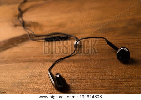 Black Little Headphones On A Wooden Isolated Background. Horizontal Frame