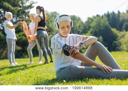Listening music. Attractive elderly blonde sitting in semi position on the grass and bowing head while being in headphones