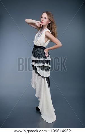 Beautiful fashion model posing on gray background.