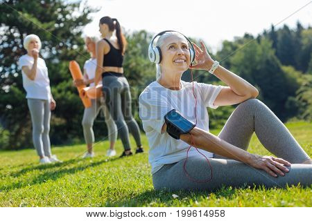 I music lover. Happy pensioner woman keeping smile on her face and relaxing after training while touching her headphones