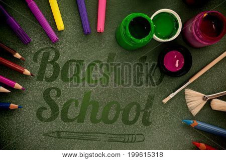 Back to school text over white background against high angle view of watercolor paints with highlighters