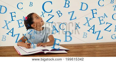 letters against young girl writing in her book against white background
