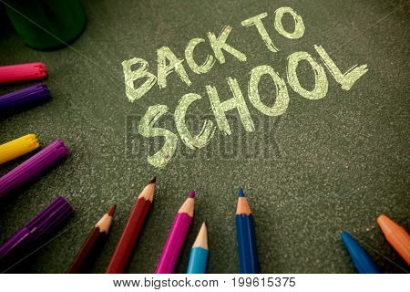 Graphic image of red back to school text against colorful pencils on table