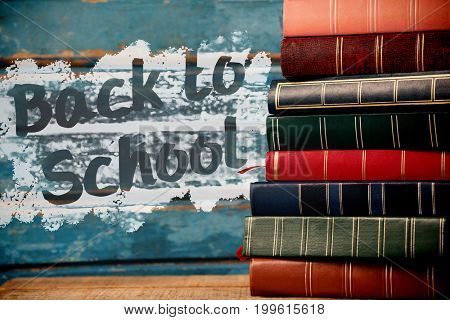 Back to school text on pink splash against colorful books stacked on table