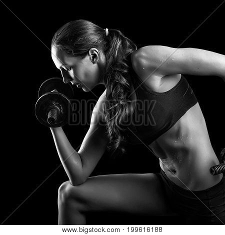 Dark contrast shot of young beautiful fitness woman with beads of sweat which training in gym. Working out with dumbbells on black background