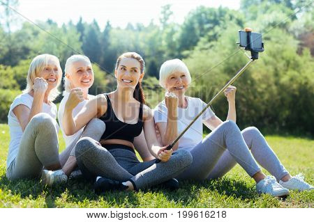 Time for photo. Group of smiling women making fists while posing on camera, sitting on the grass