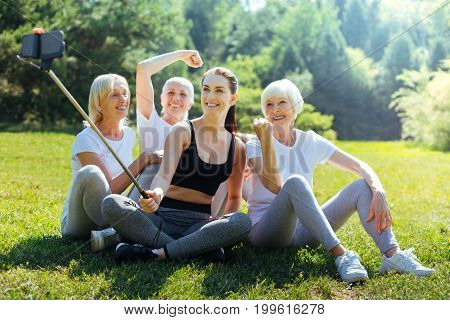 Strong spirited. Healthy females spending time with pleasure on nature and keeping smile on faces while looking at camera