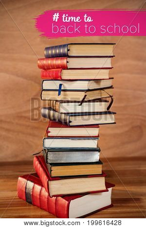 Back to school text with hashtag  against stack of books on table