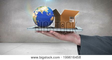 Cropped hand of man holding digital tablet against grey room