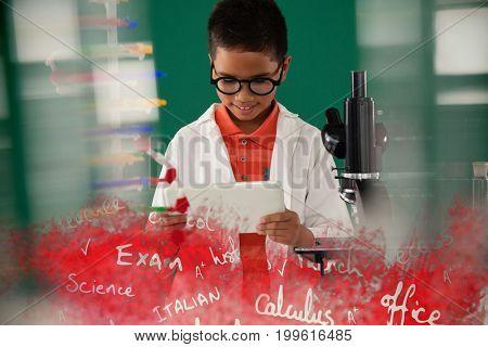 Text on black chalkboard against schoolboy using digital tablet