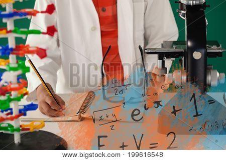 Illustrationof algebraic formulas against schoolboy writing on book against green background