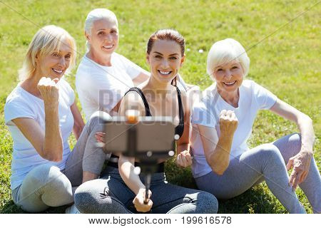 Pose on camera. Smiling women demonstrating their strength while looking at camera and being very glad